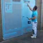 Van Straalen Schilderswerken aan het werk met het schilderen van twee metalen deuren