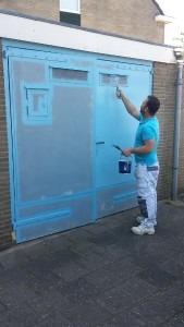 Van Straalen Schilderswerken onderhoudsschilder aan het werk met het schilderen van twee metalen deuren